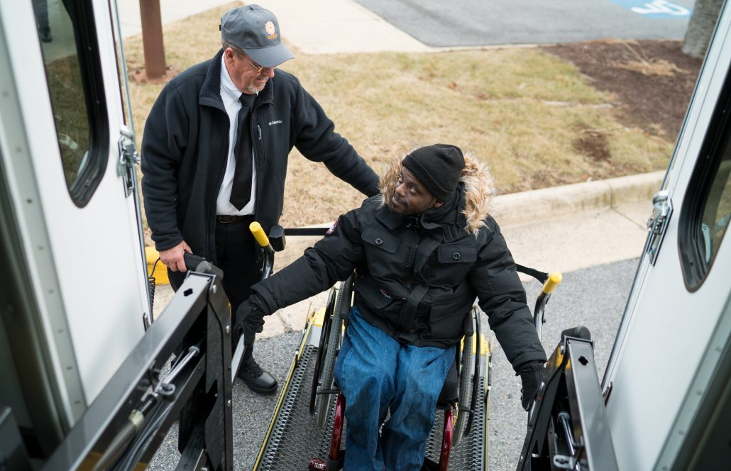brite bus driver helping out handicapped passenger